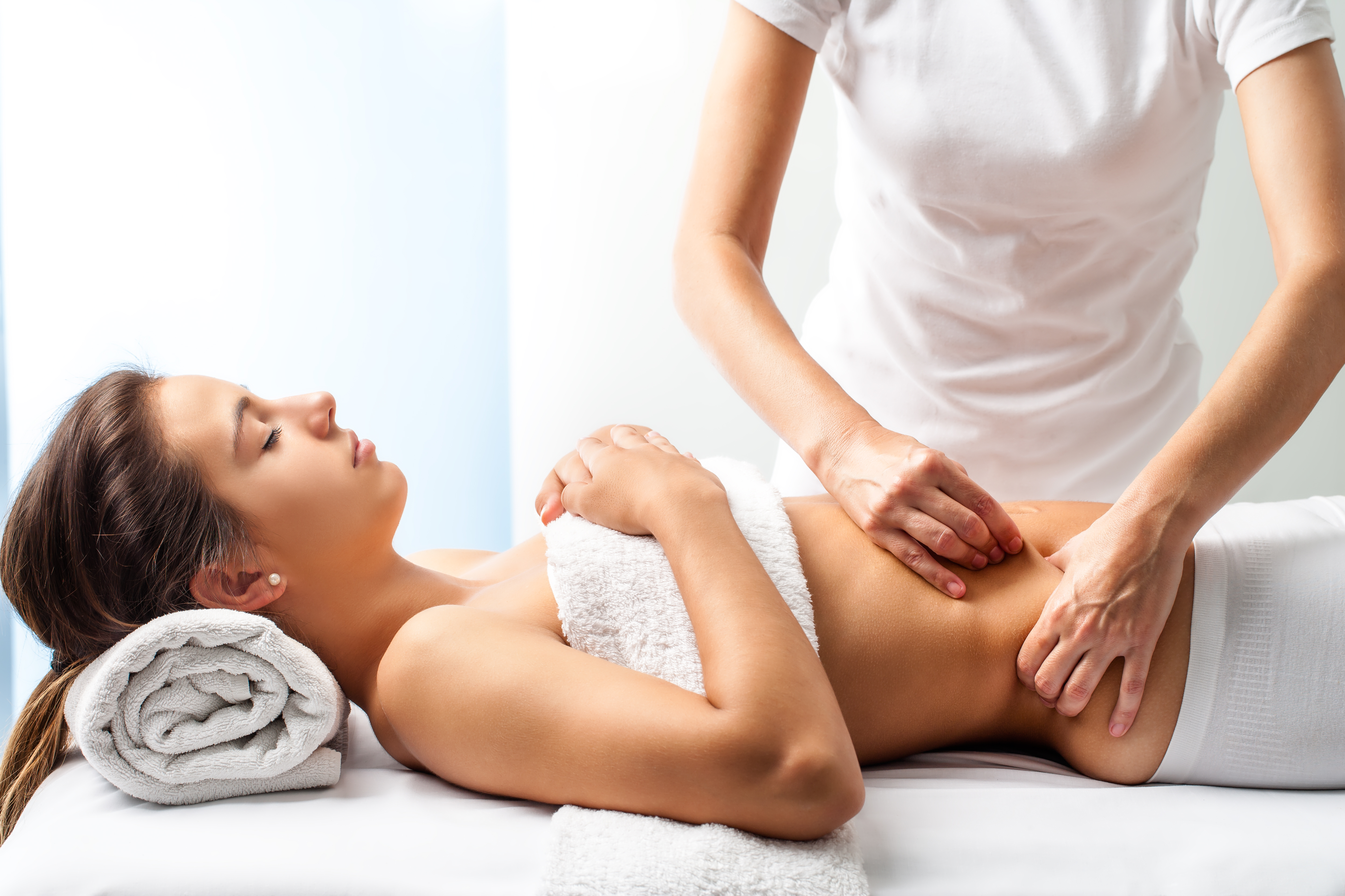 Therapist doing healing massage on female abdomen